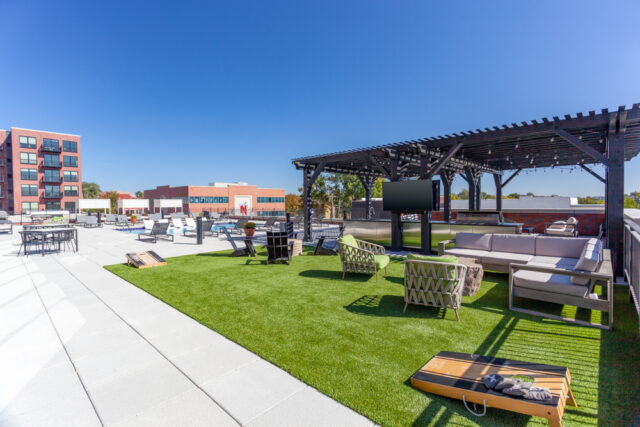 Westport, MO Apartments - Rooftop with Exterior View of Westley on Broadway Apartments Building, Sparkling Swimming Pool, and Lounge Seating