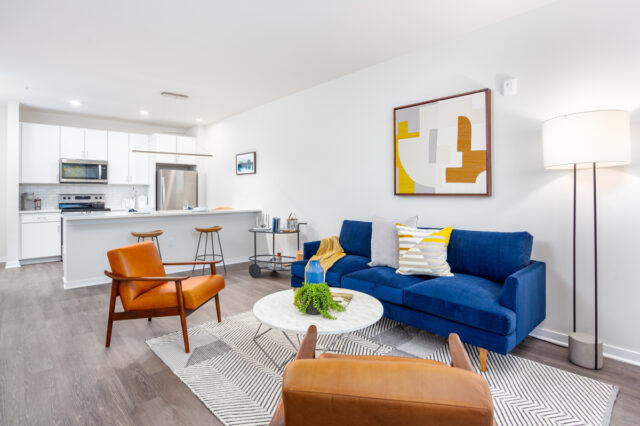 Apartments in Westport, MO - Westley on Broadway Living Room with Stylish Decor, Hardwood-Style Flooring, Large Windows, and White Textured Walls