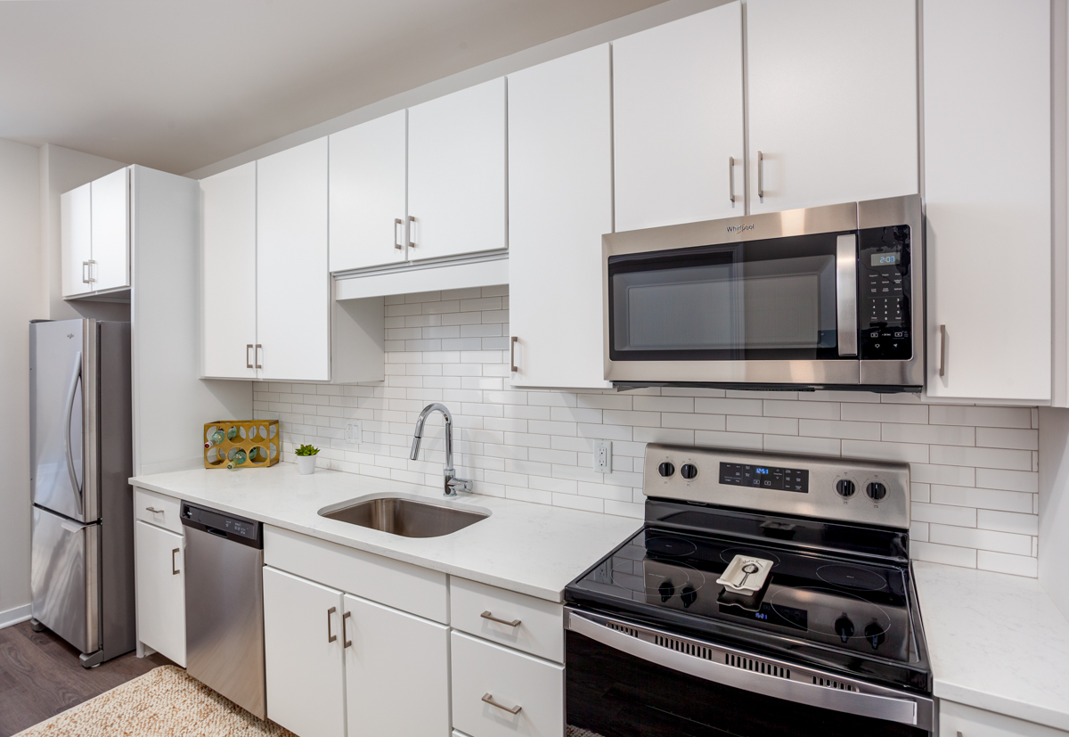 Apartments for Rent in Westport, MO - Westley on Broadway Kitchen with Whirlpool Stainless Steel Appliances, Wood-Style Flooring, and Upscale White Cabinetry
